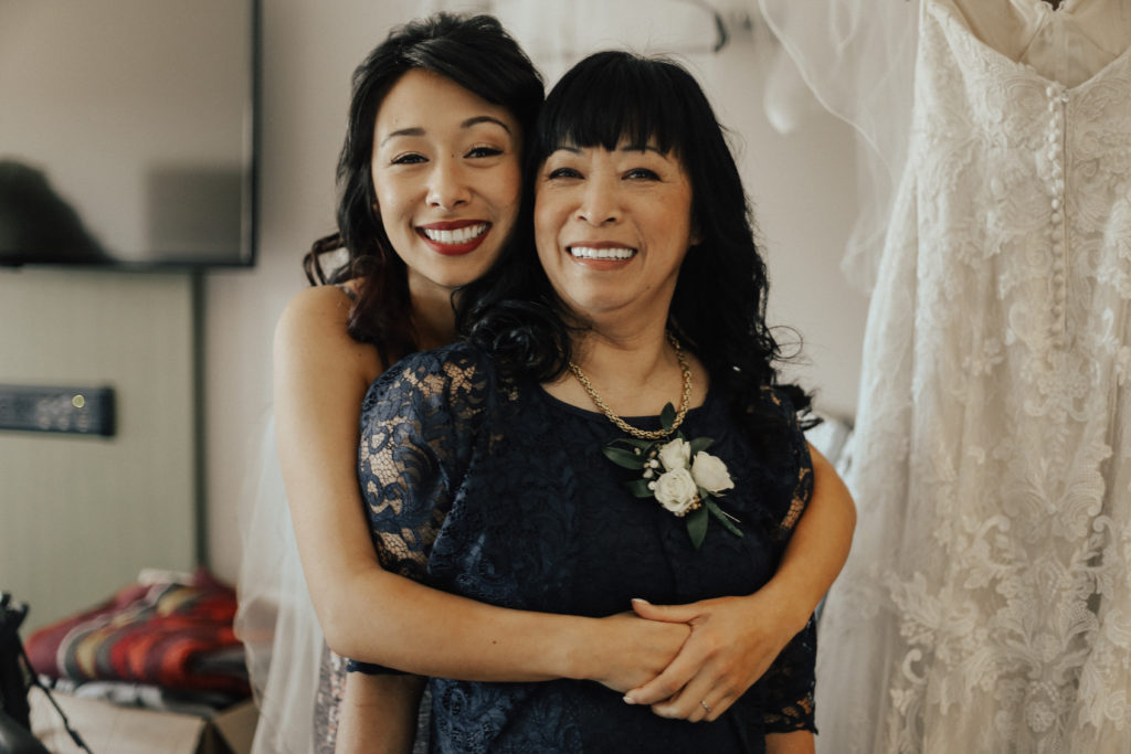 Steal of a Wedding bride hugging her mother from behind with makeup done by Erin Bradley