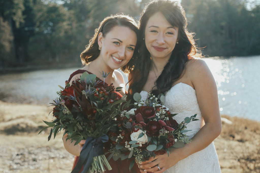 West Coast Weddings Magazine bride and bridesmaid holding up their bouquets from West Coast Weddings Magazine