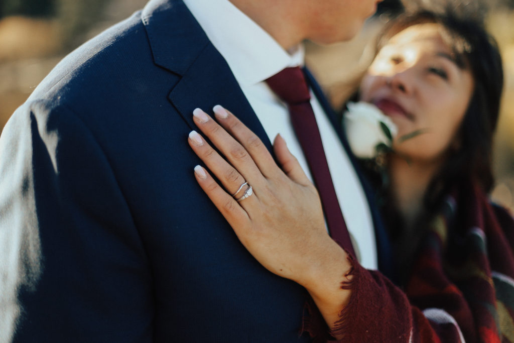 Steal of a Wedding bride's hand on groom's chest showing off wedding band and engagement ring from People's Jewellers