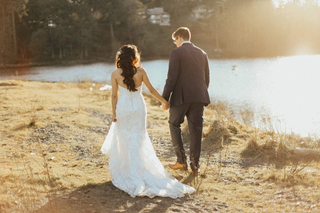 Steal of a wedding bride and groom walking shoreline holding hands shades of white bridal