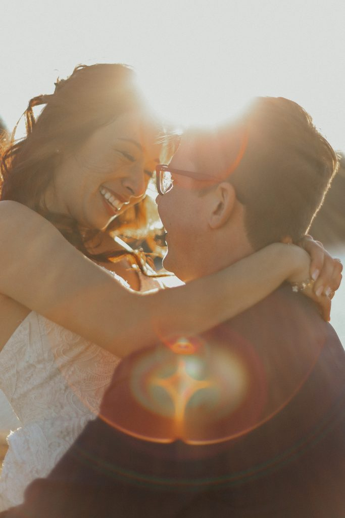 Steal of a Wedding groom holding up smiling bride with lens flare and sun in the background Jane Avenue Photography