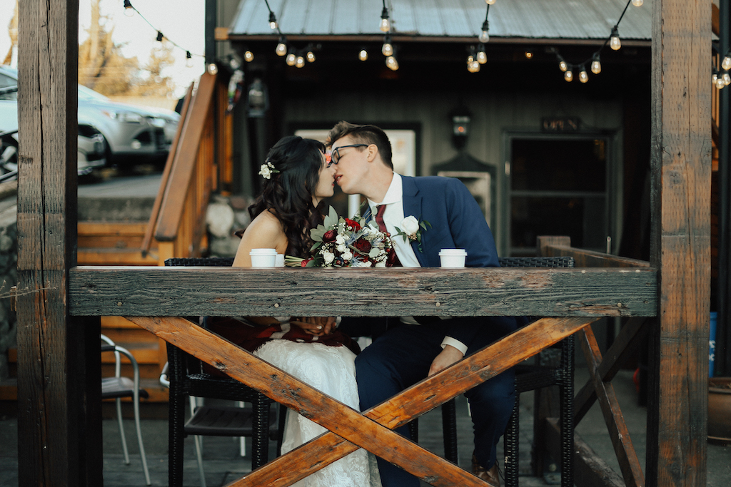 West Coast Weddings Magazine bride and groom kissing under string of lights at a coffee shop