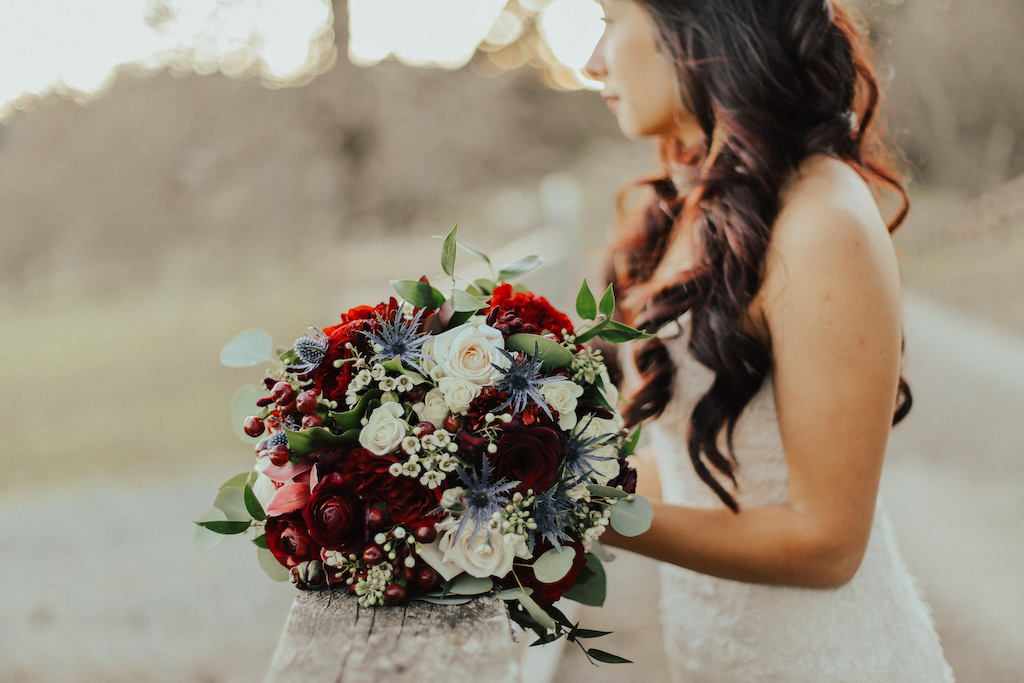 Steal of a Wedding bouquet resting on fence with red and blue flowers by West Coast Weddings Magazine and bride in the background