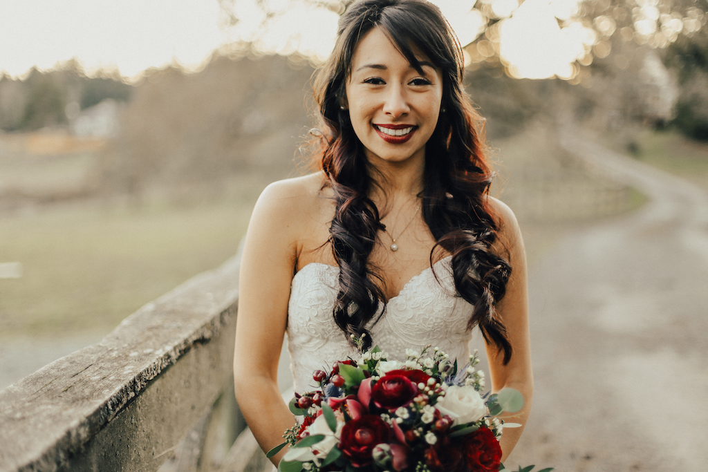 West Coast Weddings Magazine bride with curly long hair holding bouquet next to fence erin bradley