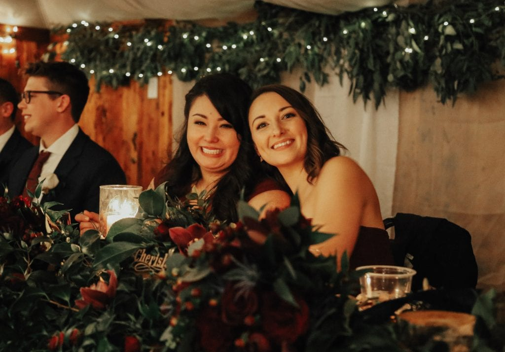Steal of a Wedding bridesmaids sitting at head table with a lot of greenery and marsala roses