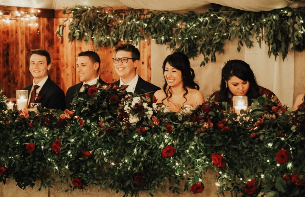 Steal of a Wedding head table with smiling bridal party and a lot of greenery, fairy lights and red roses