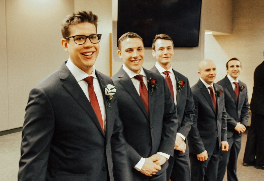 Steal of a Wedding groom and groomsmen in navy suits and marsala ties from Moore's