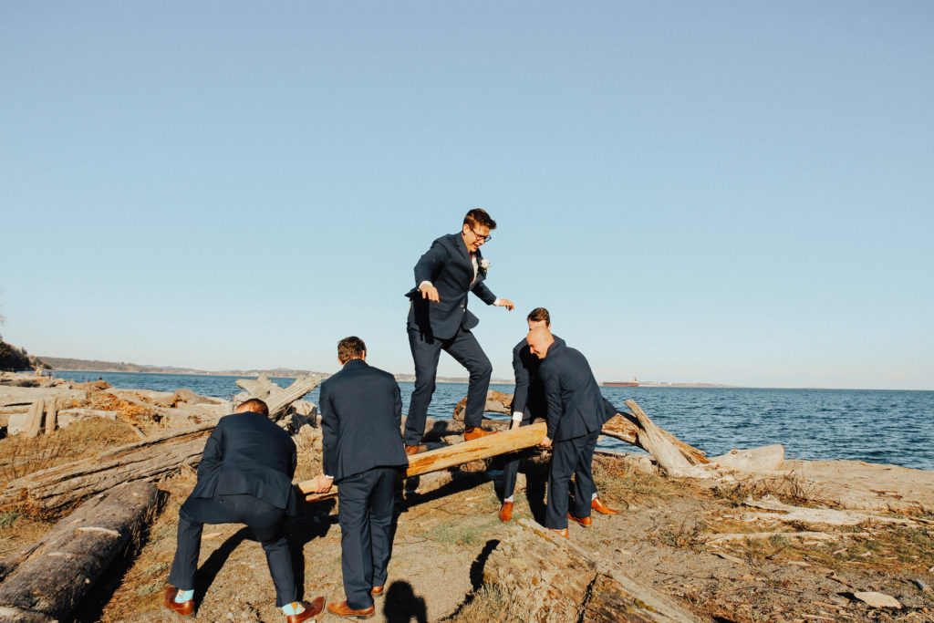 Steal of a Wedding groomsmen holding up a log at the beach with the groom standing on it