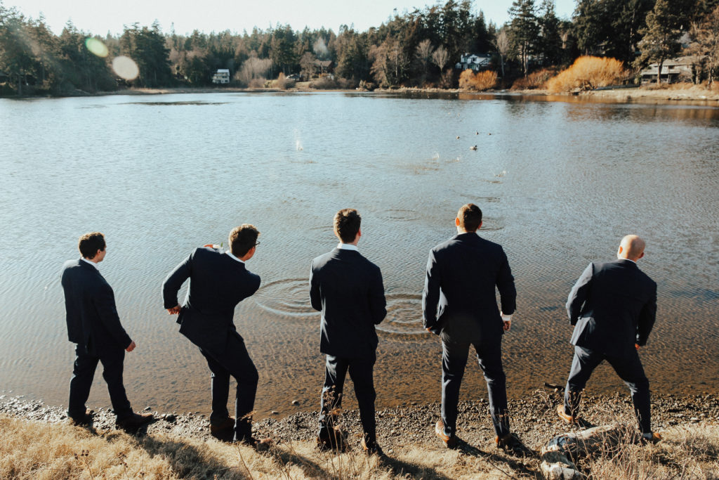 Steal of a Wedding groom and his groomsmen skipping stones by the water