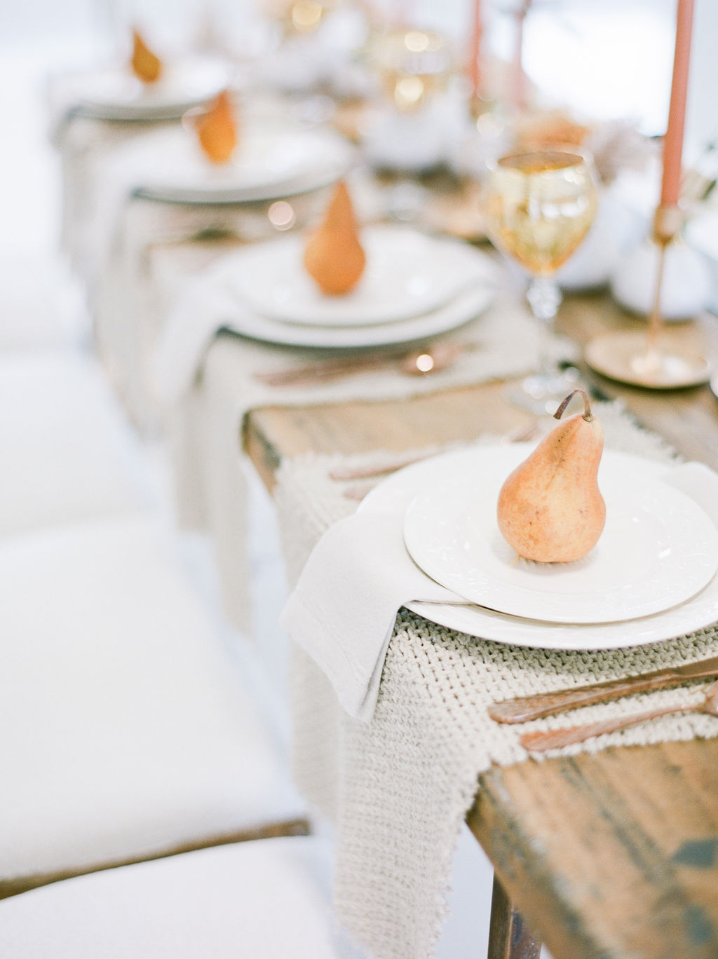 Gold pairs sit upon white plates on wood long table for newlyweds
