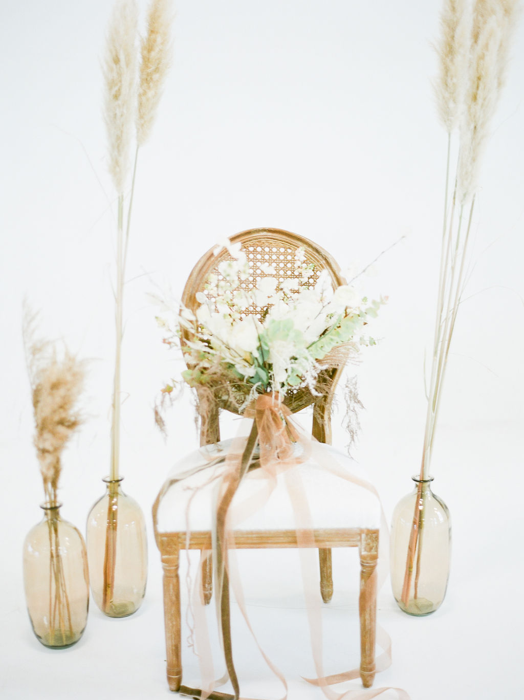 Bouquet of pampas grass and roses sit on white chair by Deborah Lee Designs Vancouver