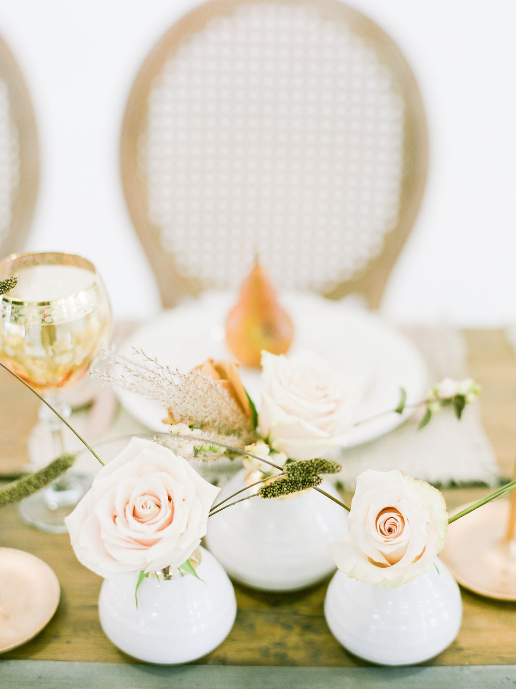 Golden pears and blush roses sot pm white dishes at wedding table