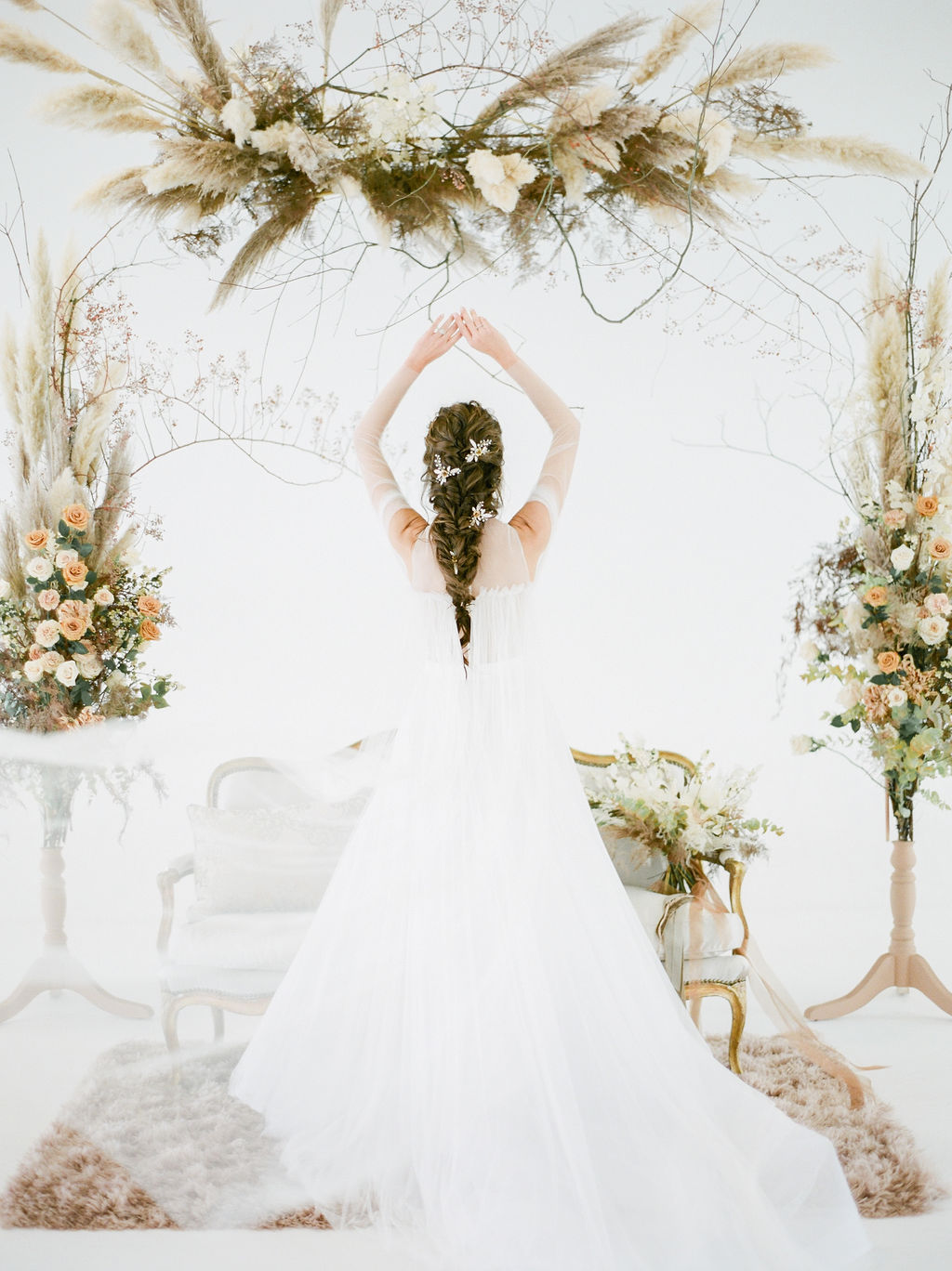 Bride holds her arms above her with floral on each side of her by