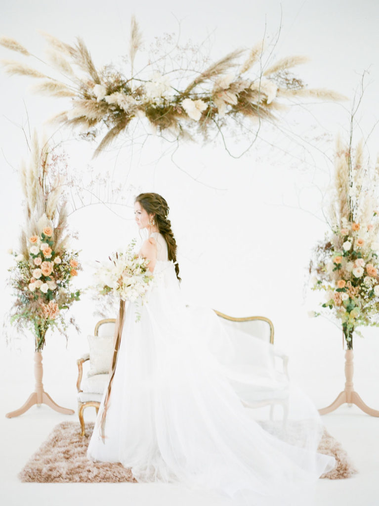 Bride in Vera Wang in white space with floral arrangements around her