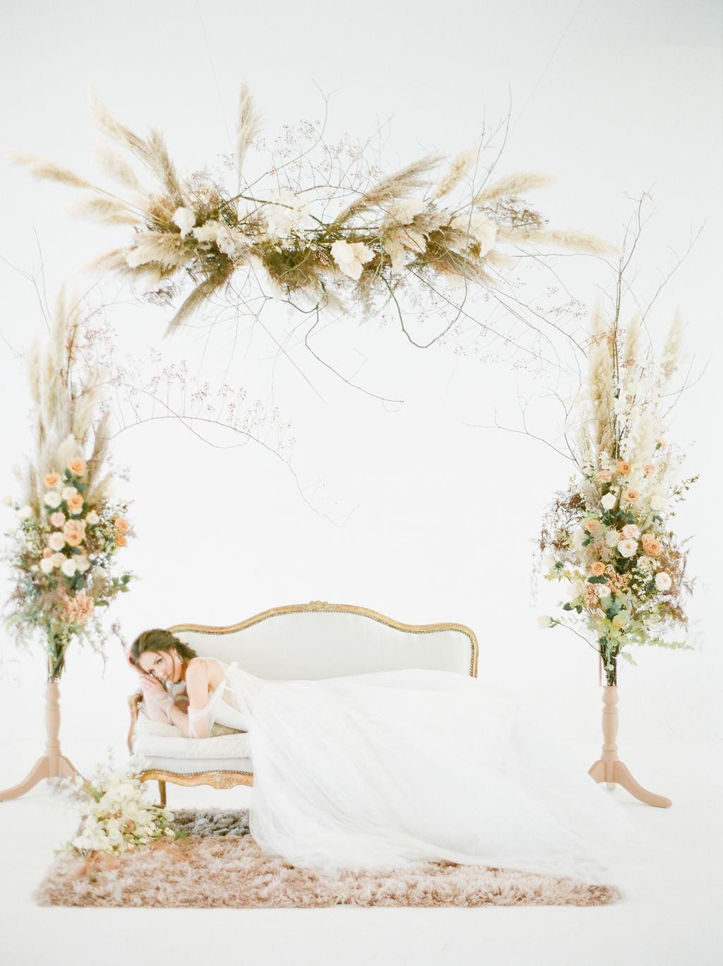 Bride on white settee surrounded by floral by Deborah Lee Designs Vancouver