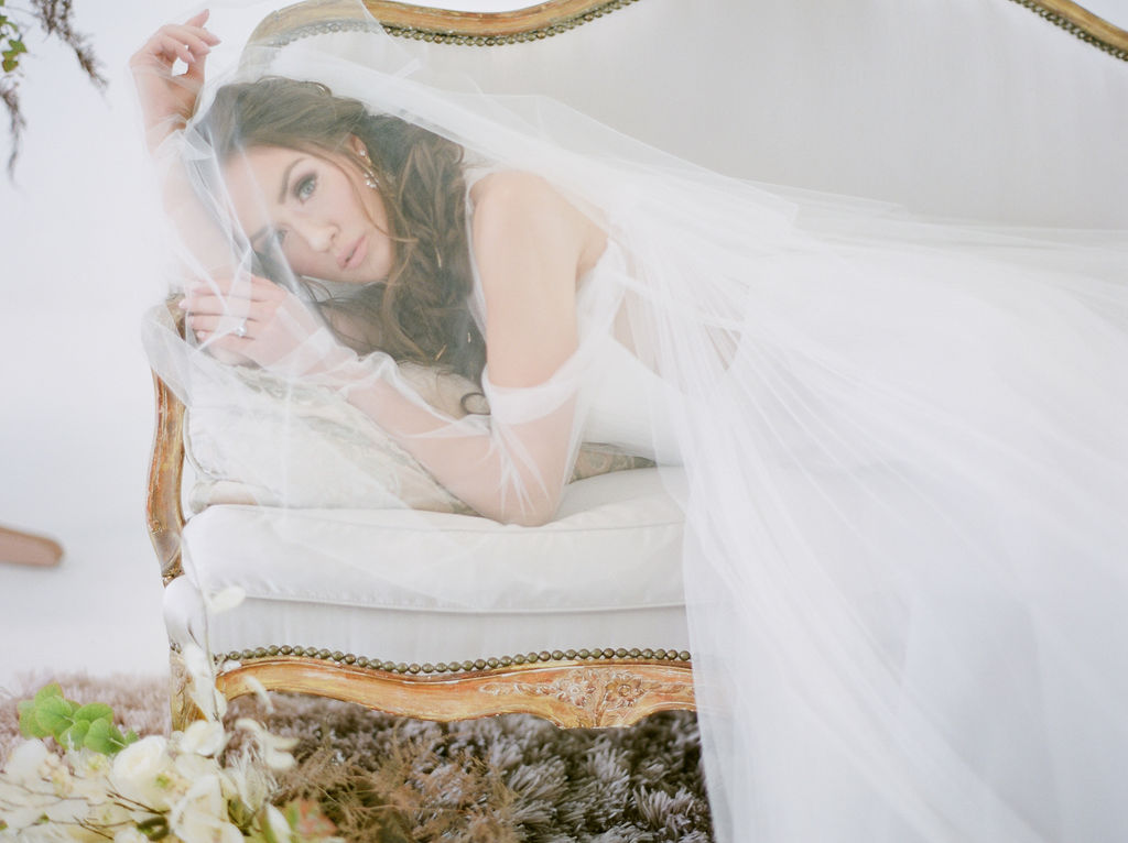 Simply Sweet Airside Space with bride laying on white settee under a veil by Vera Wang