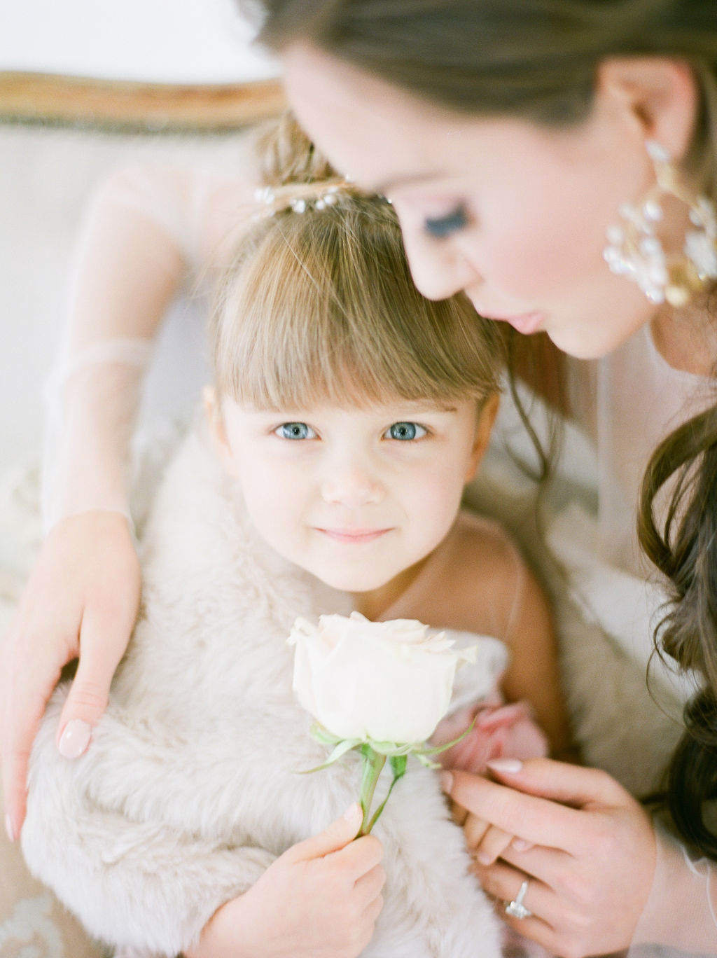 Flower girl holds white rose by Simply Sweet Photography
