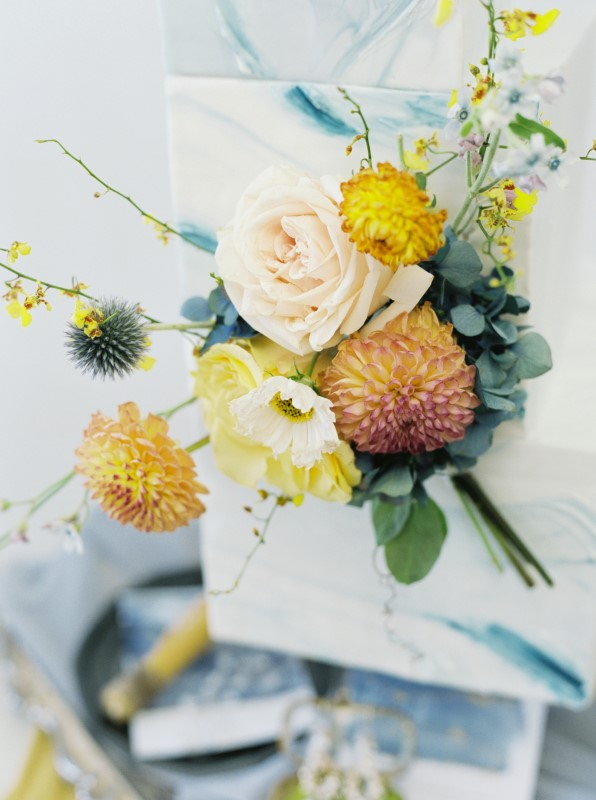 Yellow Roses and Orange and Blue Flowers on Dusty Blue Cake by Niki Xie Photography