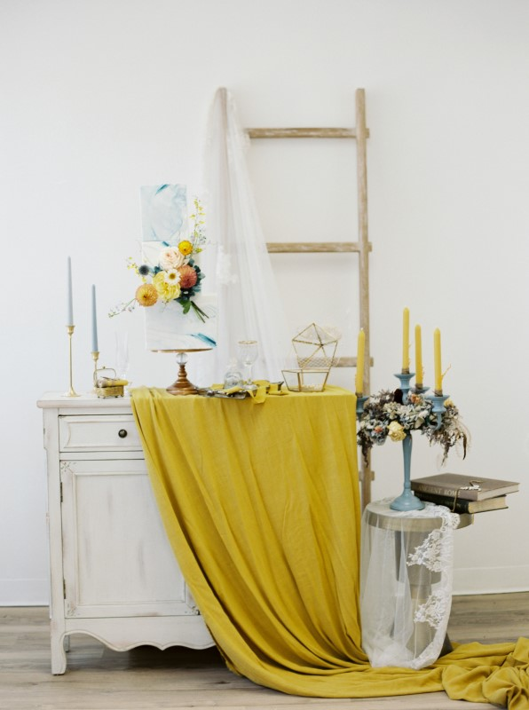 Vintage desk with yellow linen and dusty blue wedding cake and candles