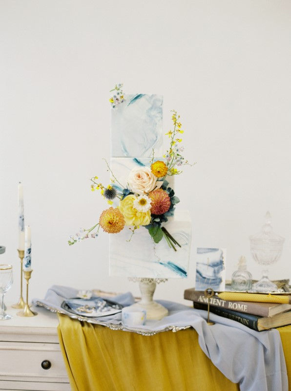 Three tier wedding cake with exquisite flowers surrounded by antique books and candles