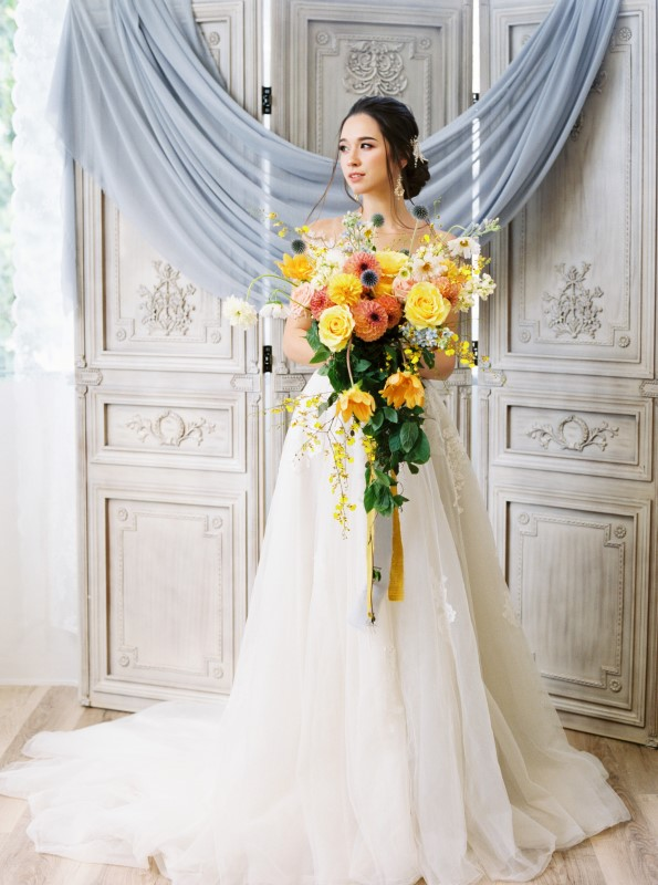 Exquisite Dusty Blue Wedding Inspiration Bride with large yellow and orange cascading bouquet by Ideal Events Vancouver