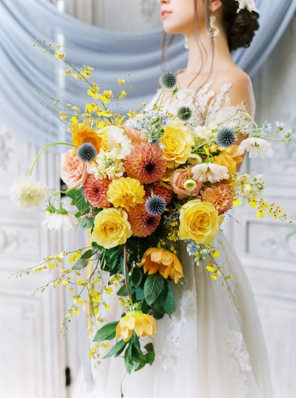 Cascading Bridal Bouquet with yellow roses and orange and blue flowers by Arizel Flowers Vancouver