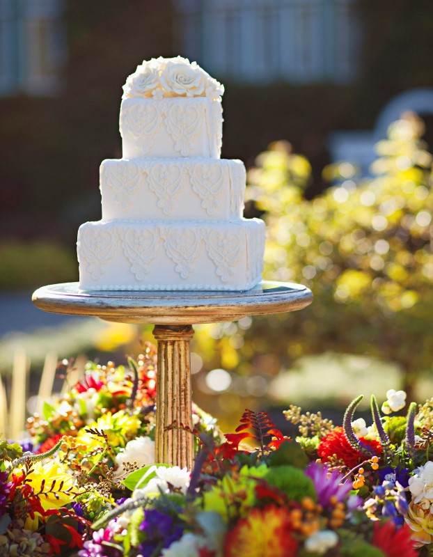 White Wedding Cake Sitting in Flower Bed at Butchart Gardens by Ooh La La Cupcakes