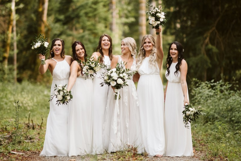 Bride and Bridesmaids in white dresses carrying bouquets of white roses and italian ruscus on Vancouver Island