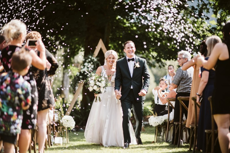 Newlyweds and Confetti after ceremony by Erin Wallis Photography
