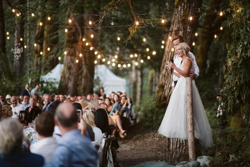 Bride and Groom stand on tree stump under globe lights giving speech to forest reception guests