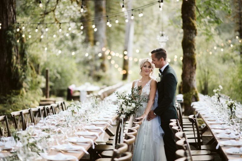 Newlyweds look over reception tables in the woods by Truffles Catering on Vancouver Island