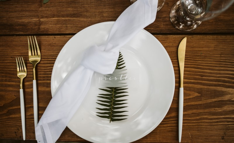White reception plate on wood table with green fern leaf by Party Mood Vancouver Island
