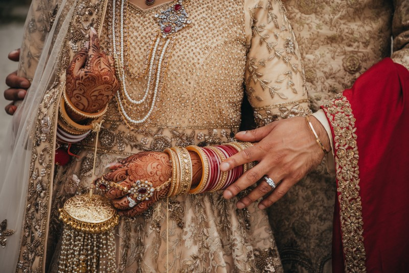 Luxury Indian Wedding Newlyweds hands with rings and henna by Pristine Allure Studio