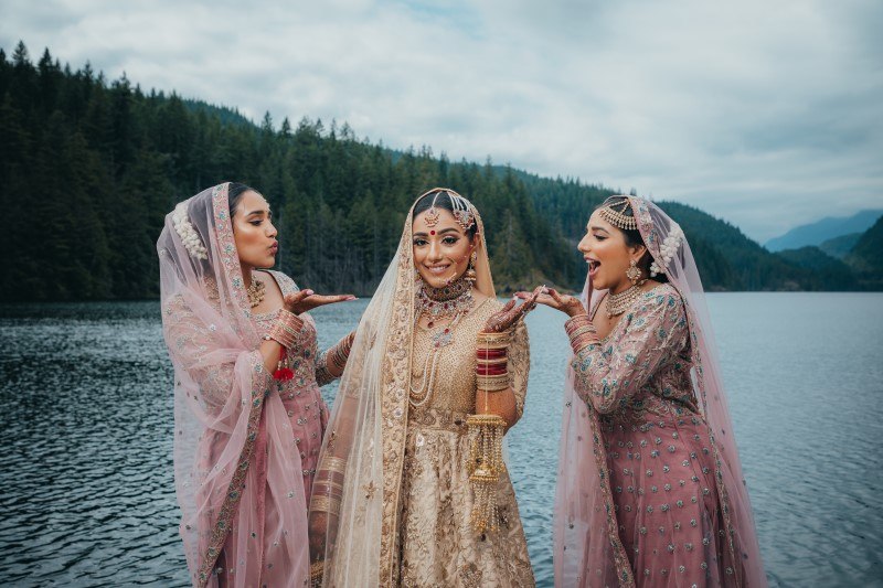 Indian Bride and Bridesmaids playfully pose in front of Rocky Mountain Lake by Dreamfinity Studios