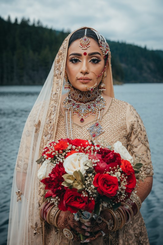 Bride in traditional Indian Saree holding bouquet of red roses