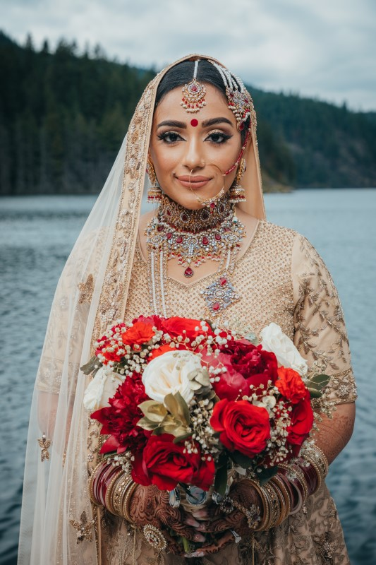 Coastal Luxury Indian Bride smiles while holding bouquet of red roses