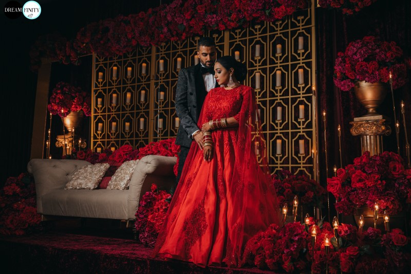Flawless Bridal Fusion Newlyweds on Traditional Indian Dias covered in scarlet red roses and gold backdrop by Universal Decor Events