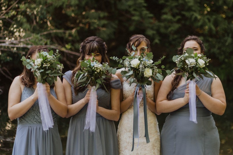 Bridal Party Holds Up Florals by Lucinda Larsen Events
