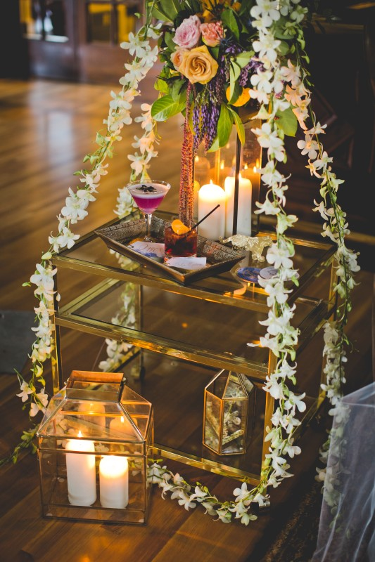 Bengal Spice white orchids strung over glass table and lit candles with Pink Cocktail