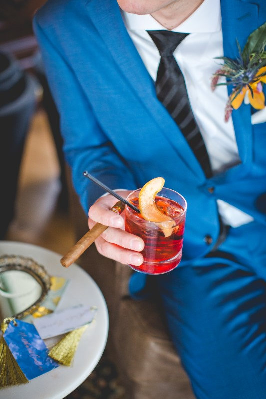 Cigar and Q Signature Drink at the Fairmont Empress held by groom wearing blue suit by Hughes Clothing