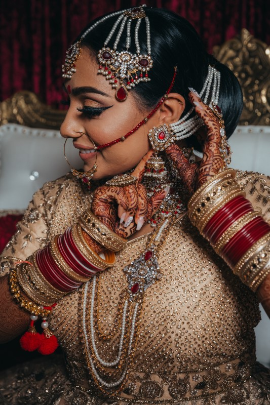 Indian Bride covered in jewelery and wearing blush saree by Dreamfinity Studios