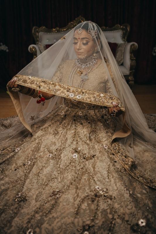 Indian Bride looking through gild edged veil by Pristine Allure Studio