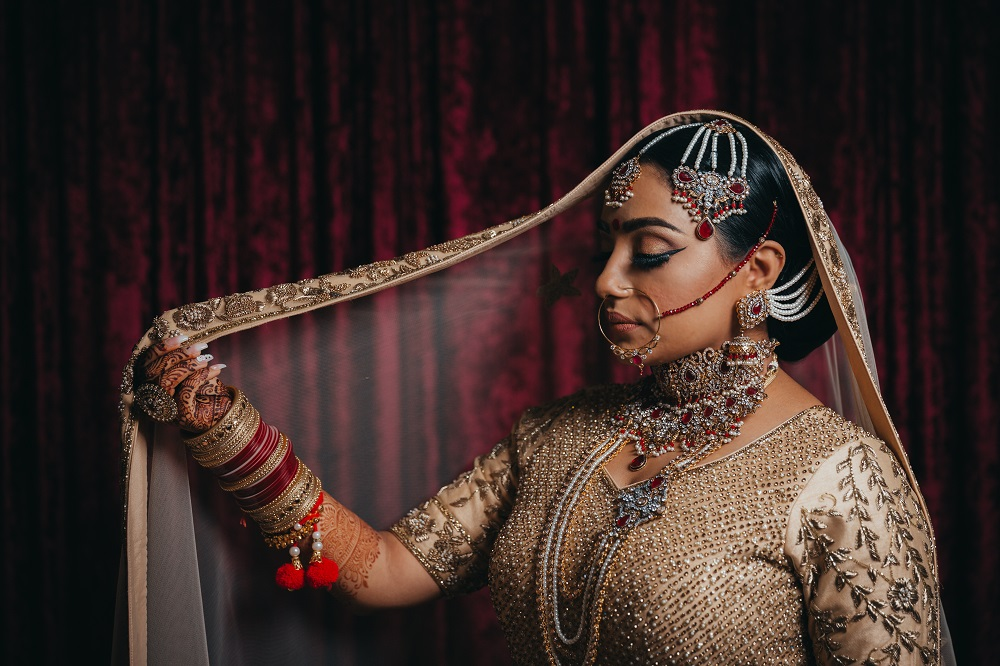 Indian Bride in blush and burgandy saree and veil by Dreamfinity Studios