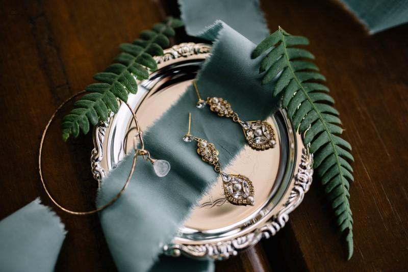 Seaside Romance Wedding Jewelery sitting in silver platter on smoky blue ribbon