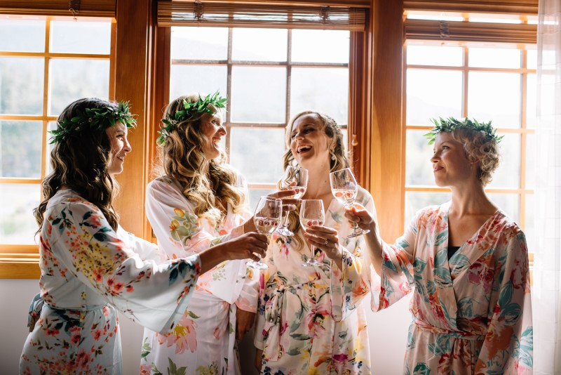 Seaside Romance Wedding Bridal Party champagne toasts while in floral robes at Telegraph Cove