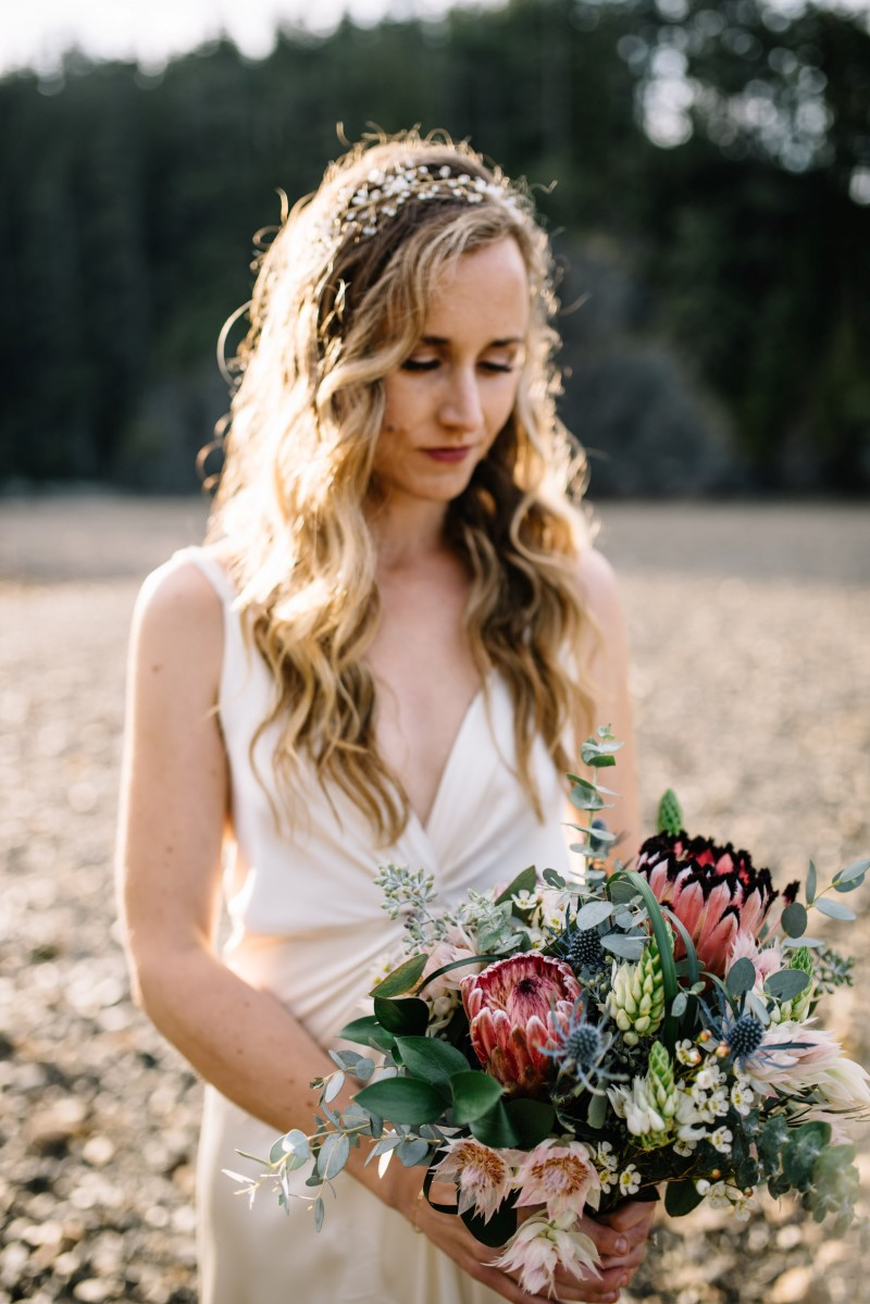 Sun Shines on Bride Holding Thrifty Foods Bouquet at Telegraph Cove