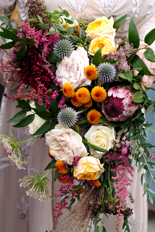 Pink Protea, blue thistle, white roses bridal bouquet by Bespoke Blossoms