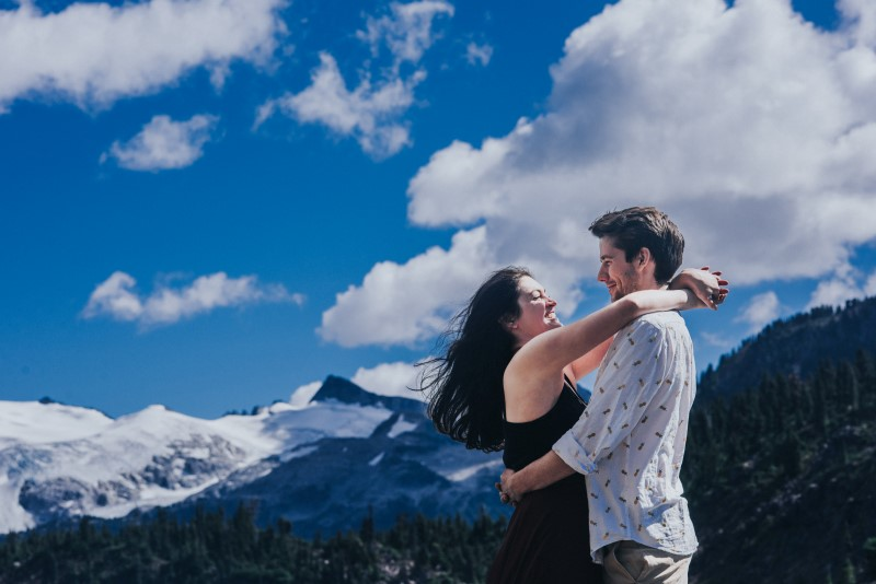 Engaged couple embrace in front of snow peaked Rocky Mountains