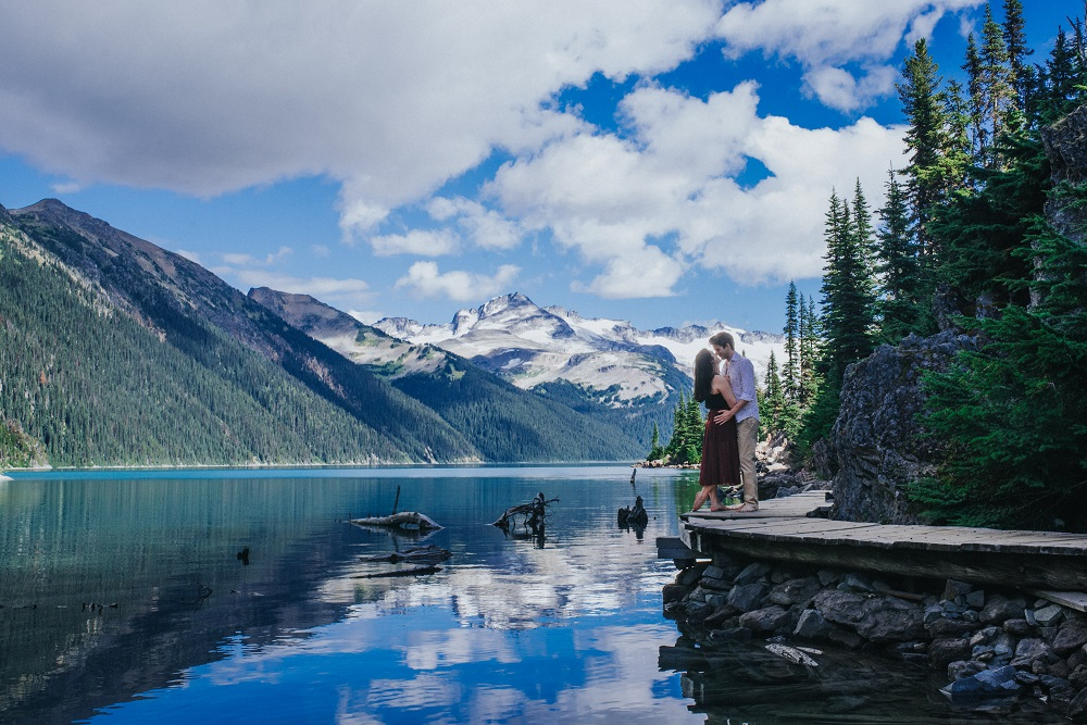 Spectacular snow peaked mountains behind engaged couple
