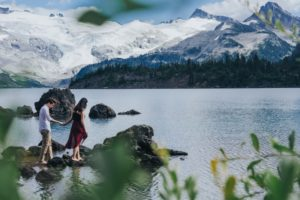 Naturally Romantic Engagement Couple walks on rocks out into BC Lake with mountains behind